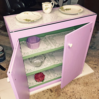 """Rescued Wares » """"Kacey"""" was a torn-out kitchen cupboard. Now painted lavender and green with lace shelf lining she is a stand alone cabinet. A glass top I already had fit her perfectly!"""